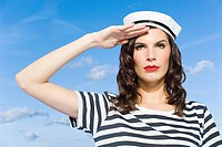 Young woman in sailor hat saluting
