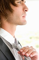 Close_up of a groom adjusting his tie