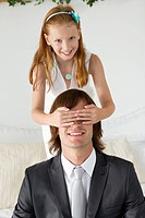 Girl covering man's eyes and smiling