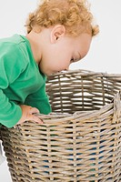 Baby boy looking into a wicker basket