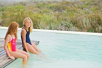 Two girls sitting on a platform at an infinity pool