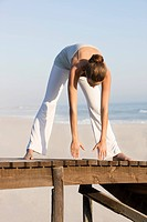 Woman stretching on a boardwalk