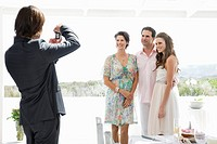 Groom taking a picture of bride with her parents at a wedding party