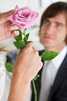 Woman holding a flower in front of a man (thumbnail)