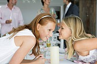 Girl whispering to her sister across a dining table