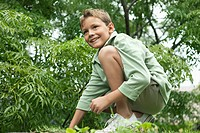 Boy playing in a garden and smiling