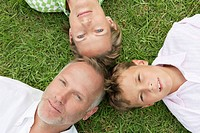 Boy with his parents lying on grass in a park (thumbnail)
