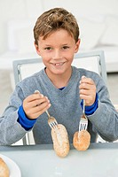 Boy poking forks on breads and smiling
