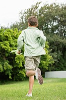 Boy running in a garden with a butterfly net