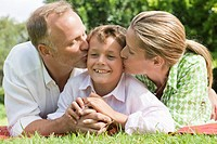 Couple kissing their son in a park