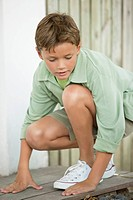 Boy crouching on a board