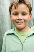 Boy holding a blade of grass in his mouth and smiling