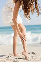 Woman removing sand from her legs