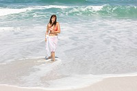 Woman walking on the beach and smiling