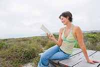 Woman sitting on a boardwalk and reading a book