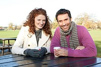 A happy couple sitting at a park table
