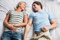 Young couple lying on bed, high angle