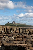 Rustic stone wall with Dunstanburgh Castle, England, Northumberland
