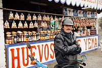 Motorcyclist in front of market stall, Lima, Peru