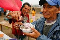 Man being served soup, Lima, Peru