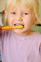 Stock photo of a 4 year old girl brushing her teeth