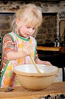 Stock photo of a four year old girl using a wodden spoon to mix up some cookie dough to make biscuits