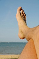 Stock photo of a mans foot as he is lying on the beach recharging his batteries on his summer holidays