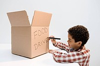 Boy writing food drive on box