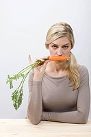 Woman holding a carrot (thumbnail)