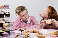 Boy and girl with doughnuts and cakes