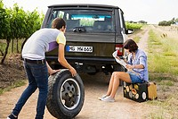 Couple by suv with tyre and map