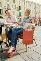 Man and woman at outdoor cafe holding shopping bag