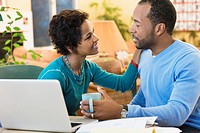 African American husband and wife sitting at computer