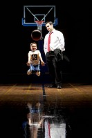 Father coaching his son on basketball court