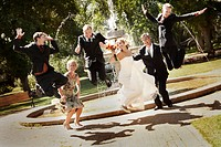 Wedding party jumping for joy in park