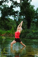 Mature woman in yoga position in lake