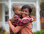 Black mother hugging son outdoors