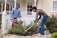 Black mother, father and daughter gardening