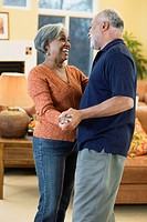 African American couple dancing in living room