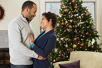 African American husband hugging wife by Christmas tree