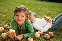 Mixed race brother and sister laying in grass with apples