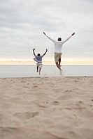Black father and son jumping on beach