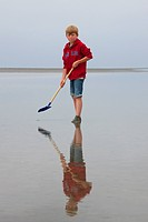 Boy with spade looking for worms on the beach at the Wadden Sea, Germany