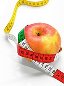 Red apple with tape measure on white with clipping path