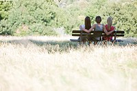 Three young people sitting on a bench in a park