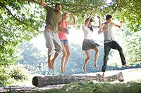 Four friends jumping from a log