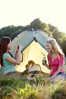 Three young women camping, one taking a photo (thumbnail)