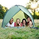 Four young people lying in a tent, looking at camera