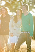 Two young couples standing in a field, smiling (thumbnail)