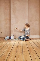 Woman sitting on floor of unrenovated room looking at colour paint swatches